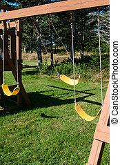 Swing H - An empty swing moving in a breeze