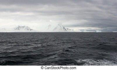 Water surface and desert snow coastline in ocean of Antarctica.