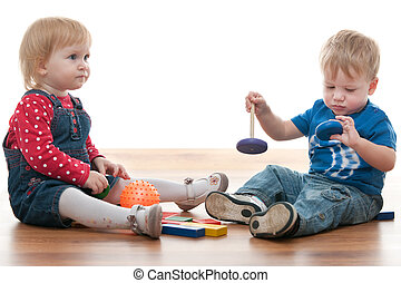 Two toddlers are playing with blocks