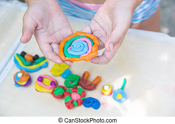 Child playing with colorful clay making animal figures....