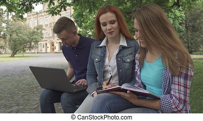 Female student writes in her exercise book on campus -...