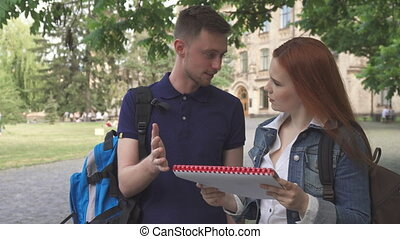Two students discuss something in notebook on campus