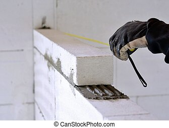 Bricklayer using a tape measure - The bricklayer measures a...