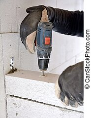 Bricklayer using a battery screwdriver - The bricklayer...