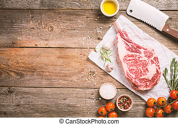 Raw tomahawk beef steak with ingredients for grilling:...