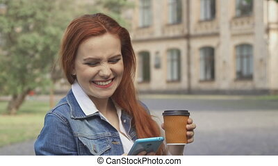Female student laughs at what she see on her smartphone on campus