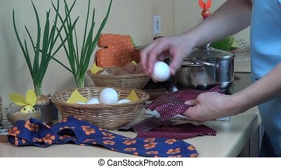 female hands put white egg into silk material. Easter eggs...