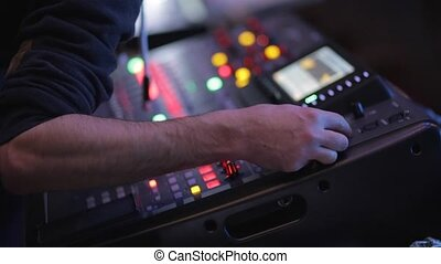 The man controls the mixer during a concert in the dark.