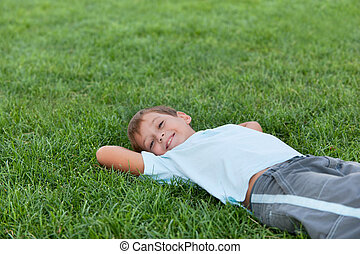 Happy boy on the green grass - A happy boy is lying on the...