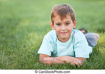 Cheerful boy lying on the lawn - A handsome smiling boy is...