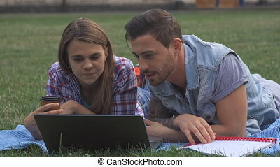 Two students discuss something on laptop on the lawn