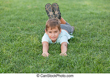 Smiling boy on the summer meadow - A smiling boy is lying on...
