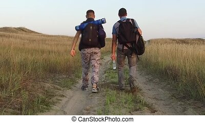 tourists on the nature. two tourists go on the road trip with men's backpacks nature slow motion video