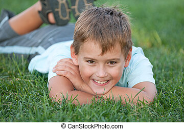 Closeup portrait of a smiling boy on the grass - A smiling...
