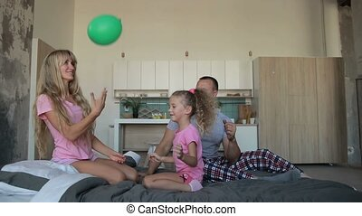 Carefree family in pajamas playing together on bed -...