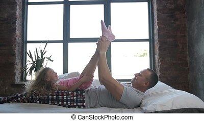 Joyful dad lifting cute curly daughter up in bed - Caring...