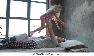Happy father letting his daughter fly in bedroom - Loving...