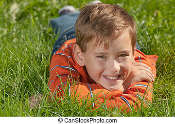 Smiling boy - A handsome smiling boy is smiling lying on the...
