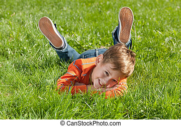Smiling boy lying on the grass - A handsome smiling boy is...