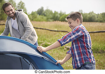 Son helping his father on the camping