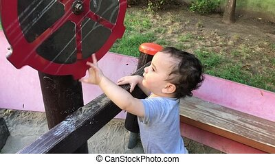 Two year old boy spining wheel - Toddler plays in a...