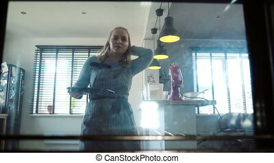 View inside: young beautiful woman opens the oven and puts...