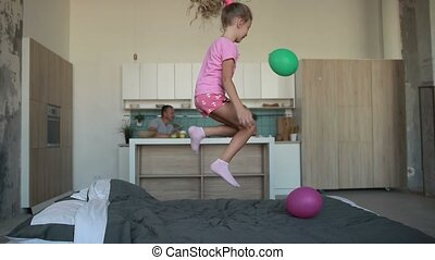 Cute little girl in pajamas jumping on bed - Excited little...