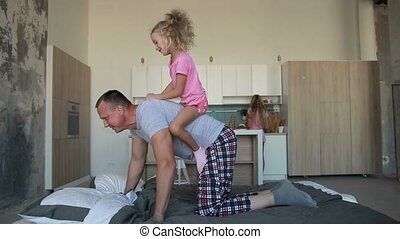 Father giving piggyback ride to daughter at home - Happy mad...