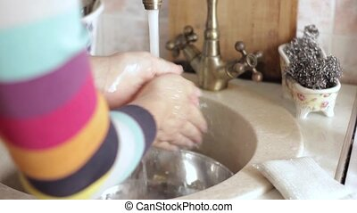 Woman washing her hands in sink in a kitchen.