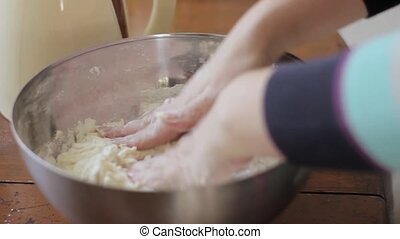 woman hands kneading dough on table. cooking food on a...