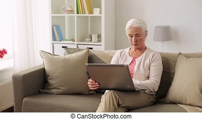happy senior woman with laptop computer at home -...