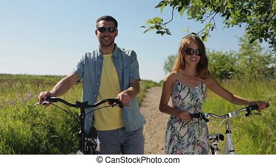 happy young couple with bicycles walking in summer - people...