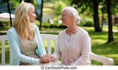 daughter with senior mother talking on park bench - family,...