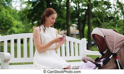happy mother with smartphone and stroller at park -...