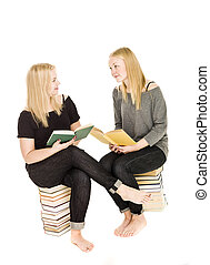 Girls sitting on pile of books
