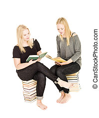 Girls sitting on piles of books