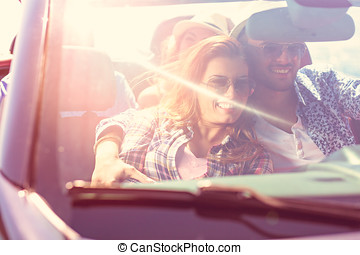 Couple with friends driving in the sunset