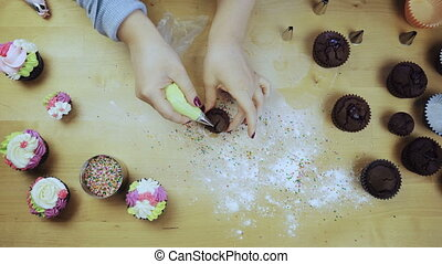 Top view of female hands decorating the chocolate cupcakes....