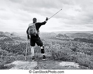 Disabled man on crutches on rock. Hurt knee in neoprene metal knee braces and man hold forearms crutches.