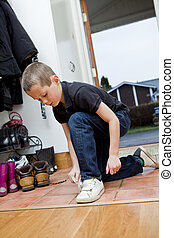 Little Boy tying his shoes before he gets outdoor