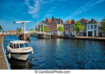 Spaarne river with boat and Gravestenenbrug bridge in...