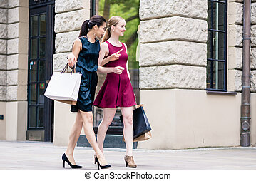 Two fashionable women carrying paper bags while shopping in summ