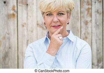 Portrait of an active senior woman looking at camera with a pens