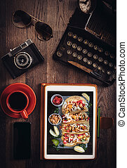 Food blog concept with tortilla sandwiches on tablet pc on...