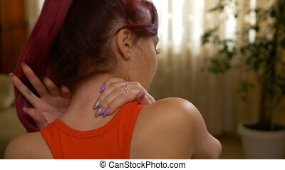 Closeup of teenage girl rubbing her shoulder and neck as if...