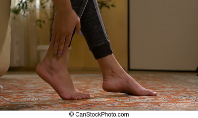 Fit woman massaging sore barefoot sole to relieve the pain...