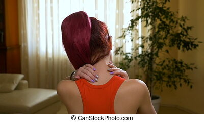Young pained woman massaging her back of neck to heal the...
