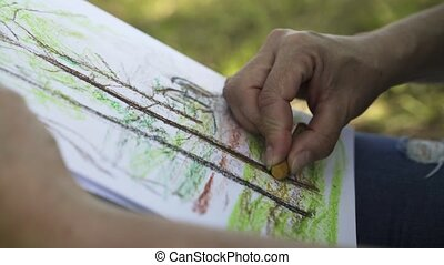 Close up of a woman drawing a tree in a park