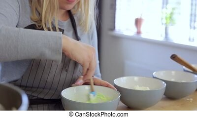 Young beautiful woman making the colored cream for desserts,...