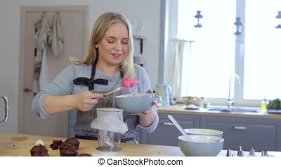 Blonde female making cream for decorating cupcakes, doing...